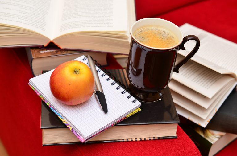 Bild på böcker, kaffe, skrivmaterial och äpple. Allt man behöver för att göra en bra översättning.