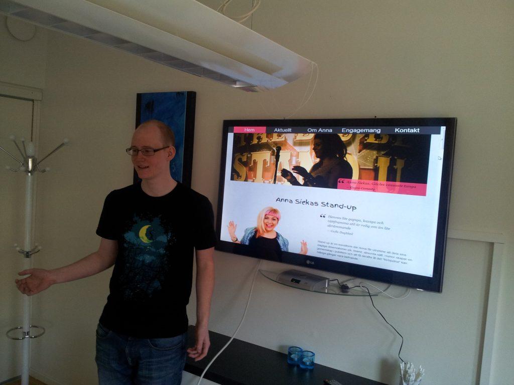 Simon Olsson står framför en skärm som visar den nya webbplatsen
