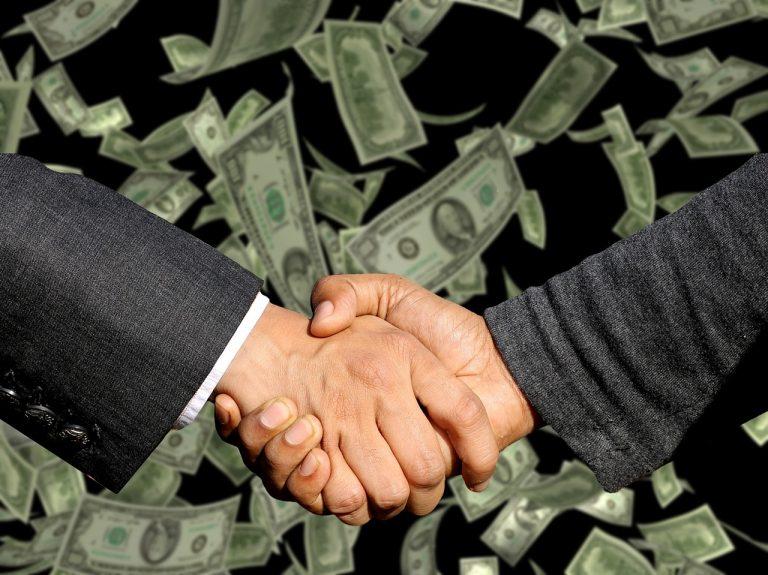 Två händer som skakar hand. I bakgrunden flyger det pengar. Som snö.