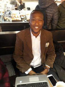 Elmi Abdiaziz, somalier, sitter i prydlig brum kavaj och vit skjorta. I bröstfickan har en mönstrad näsduk. Han ser glad ut.