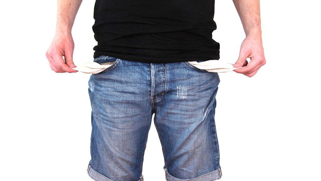Person i jeans med fickorna vända ut och in.