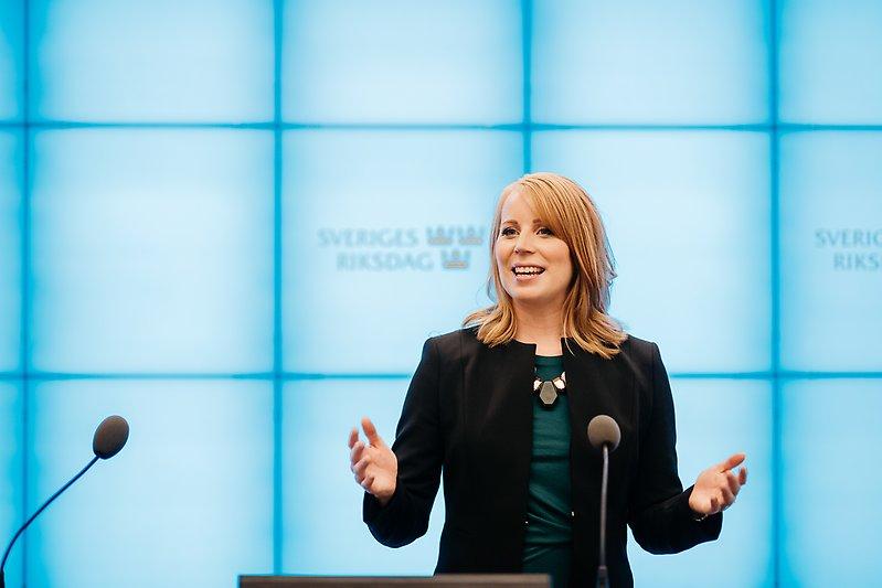 Annie Lööf står och talar mot blå bakgrund