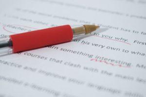 En röd penna som ligger på ett papper med text. Texten har röda markeringar.