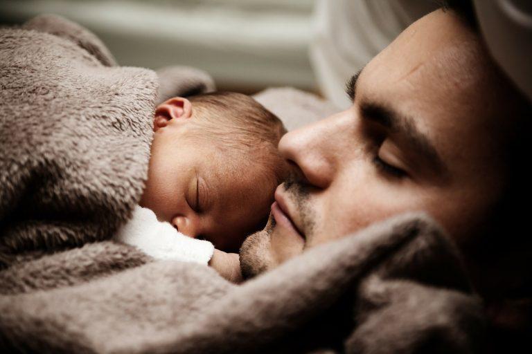 En pyttebebis ligger på sin pappas bröstkorg. Båda sover.