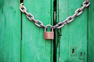 En grön port, låst med en kedja och ett hänglås. Här kommer ingen in!