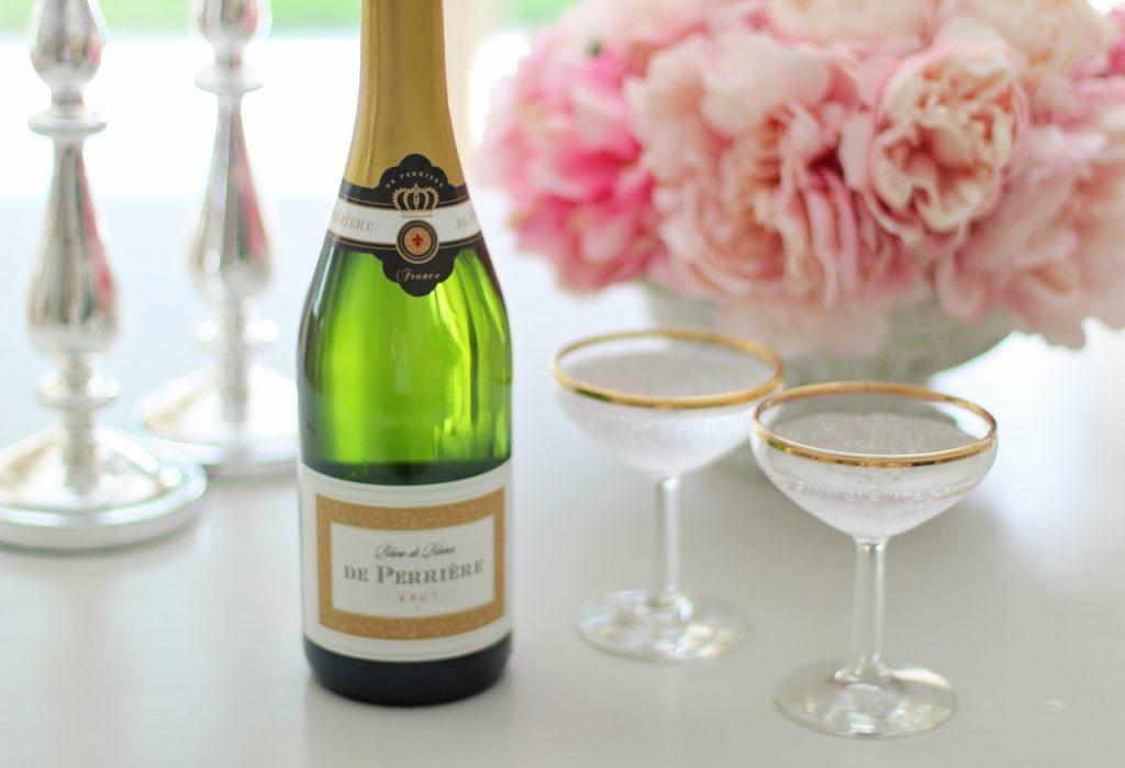 Grön champagneflaska med två gammaldags champagneglas med guldkant. I bakgrunden rosa blommor. Kanske rosor.