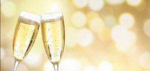 Två glas champagne mot en guldgul bakgrund.