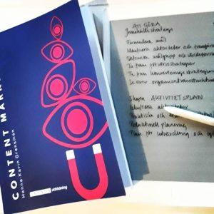 En bild på boken Content Marketing (omslaget är blått och rosa, texten vit). Bredvid ligger en remarkable (en skrivplatta).