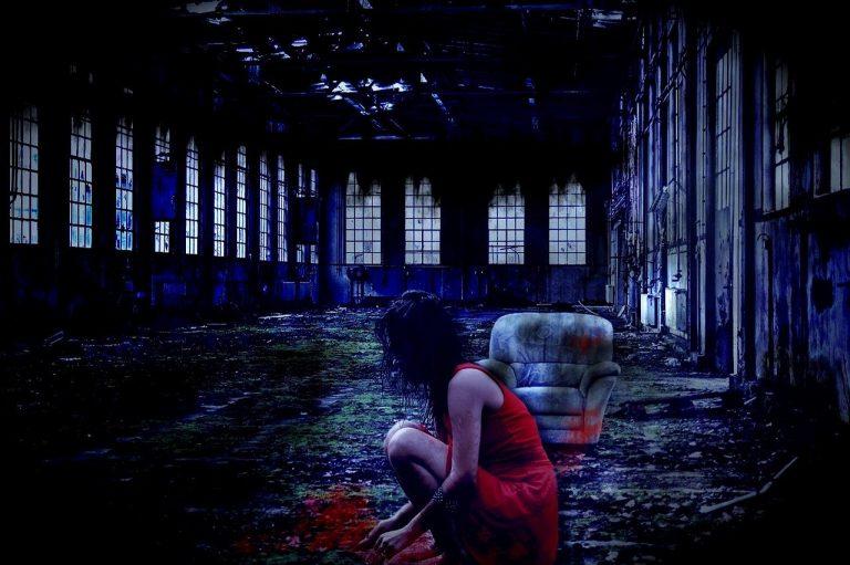 Blåtonad fabrik. Slitet, smutsigt. Kvinna i rött sitter på golvet. Det svarta håret är rufsigt. Man ser inte hennes ansikte.